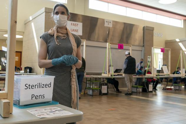 A poll worker in Sun Prairie, Wis., is seen during the state's April 7 primary. A record number of Wisconsin voters are expected to vote by mail this fall, but polls indicate Republicans are far more likely to vote in person, which has some GOP officials