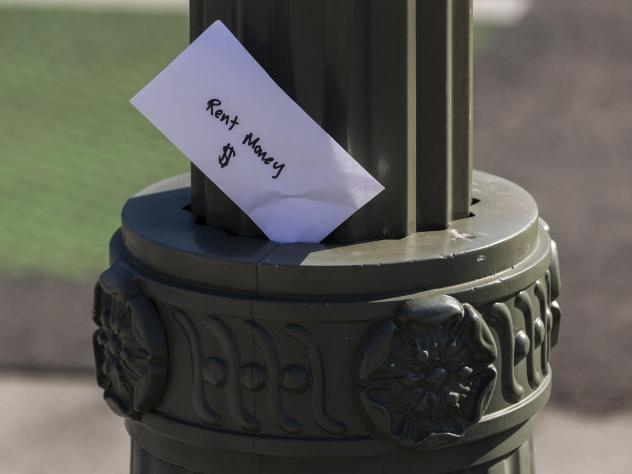 """A paper envelope written with the words """"Rent Money $"""" is left tucked in a lighting pole in April in the Boyle Heights area of Los Angeles. Amid massive job losses due to COVID-19, California Gov. Gavin Newsom signed an extended eviction moratorium on Mo"""
