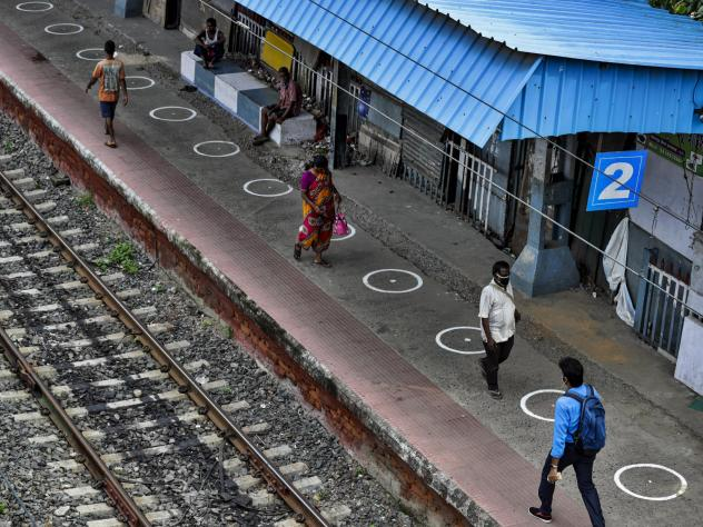 People walk through a railway station platform marked with circles to maintain physical distance in Kolkata, India, Monday. India's increasing coronavirus caseload made it the pandemic's second-worst-hit country behind the United States.