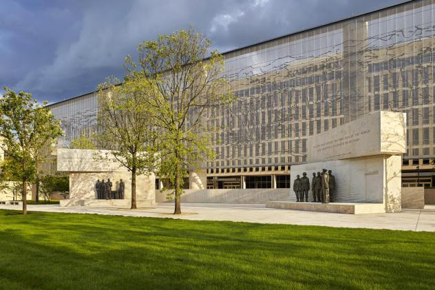 """The Dwight D. Eisenhower Memorial in Washington, D.C., will be dedicated on Thursday. A stainless steel, woven """"tapestry"""" made by artist Tomas Osinski stands behind the statues and depicts the cliffs at Normandy."""