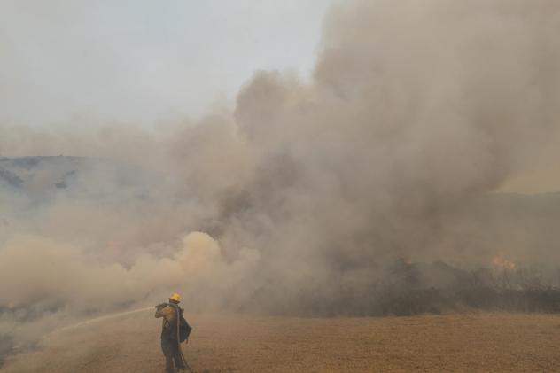 A firefighter sprays water on a controlled burn Sunday while fighting the Dolan Fire near Big Sur, Calif. Millions of acres have burned in California and neighboring states this year.