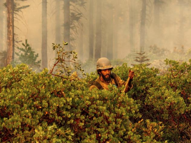 Firefighter Cody Carter battles the North Complex Fire on Monday in Plumas National Forest in California.