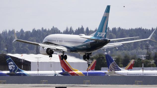 A Boeing 737 Max heads to a landing past grounded Max jets at Seattle's Boeing Field after a test flight in June. It was the first of three days of recertification test flights that mark a step toward returning the aircraft to passenger service.