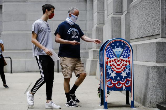 Benjamin Graff, center, and his son Jacob Graff, 19, drop off their mail-in ballots for the Pennsylvania primary election, in Philadelphia, on June 2, 2020. The state Supreme Court affirmed Thursday that counties may use drop boxes for voters casting mai