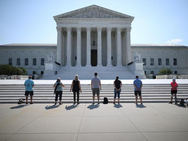 Demonstrators pray in front of the U.S. Supreme Court on July 8, a day the court ruled that employers with religious objections can decline to provide contraception coverage under the Affordable Care Act. With the death of Ruth Bader Ginsburg, the ACA's