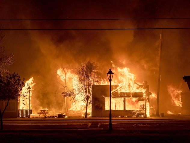 Buildings are engulfed in flames as a wildfire ravages Talent, Ore., on Sept. 8, 2020. Unfounded rumors that left-wing activists were behind the fires went viral on social media, thanks to amplification by conspiracy theorists and the platforms' own desi