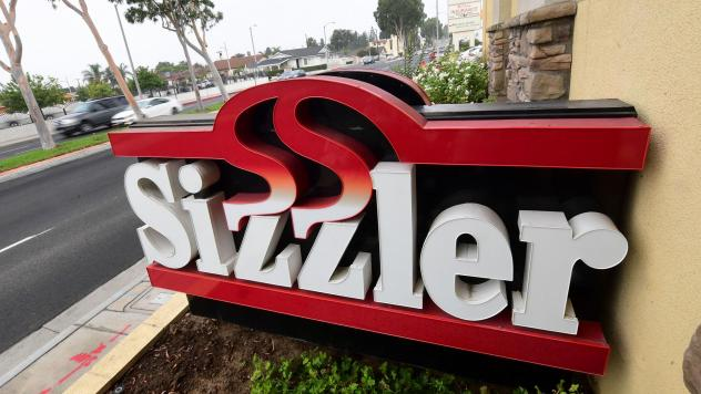Sizzler USA has filed for bankruptcy as a result of the COVID-19 pandemic and related restrictions. Here, drivers pass a closed Sizzler restaurant in Montebello, Calif.