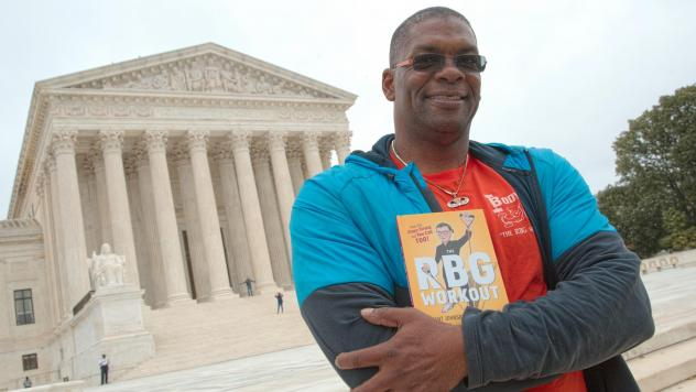 """Bryant Johnson, who was Justice Ruth Bader Ginsburg's personal trainer, poses at the court in 2017 with his book, """"The RBG Workout: How She Stays Strong ... and You Can Too!"""""""