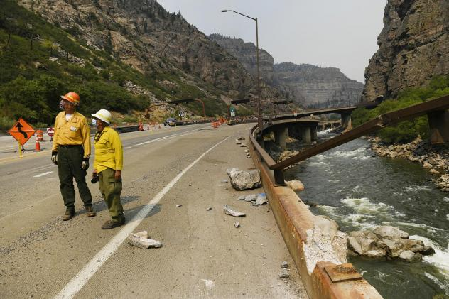 Great Basin National Incident Management One Team Public Information Officers Wayne Patterson, left, and Mike Ferris, center, check out rock fall that fell from high cliffs causing damage onto I-70 below making it dangerous for passing vehicles during th