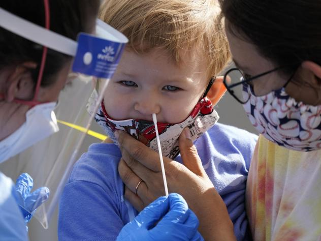 Penny Brown, 2, is held by her mother, Heather Brown, as her nose is lightly swabbed during a test for COVID-19 in Seattle last month. A survey of state health department website data shows severe illness and death among child cases of COVID-19 is rare.