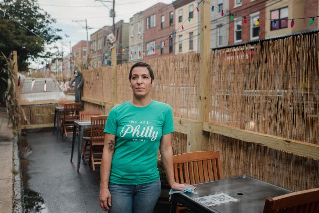 Danielle Renzulli, owner of 12 Steps Down Bar in Philadelphia, poses by the tables she has set up in what used to be parking spots. She was expecting some negative reactions from neighbors, given how valuable parking is in the area, but to her surprise,