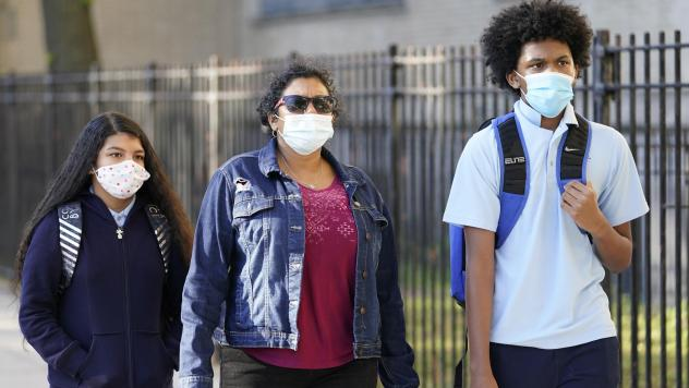 A mother accompanies her children as they arrive for the first day of in-person classes at Erasmus High School in Brooklyn's Flatbush neighborhood.