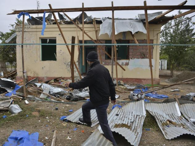 A man walks past a house destroyed by shelling during fighting over Nagorno-Karabakh in Agdam, Azerbaijan, on Oct. 1. The International Committee of the Red Cross says civilian deaths and injuries have been reported.