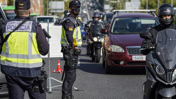 Police officers man a roadside checkpoint in Madrid Friday as travel restrictions are imposed to cope with a new wave of coronavirus infections.