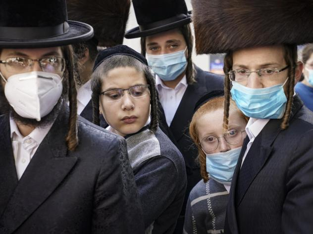 Members of the Orthodox Jewish community gather around a journalist as he conducts an interview on a street corner, last Wednesday, in the Borough Park neighborhood of the Brooklyn borough of New York. Gov. Andrew Cuomo moved to reinstate restrictions on