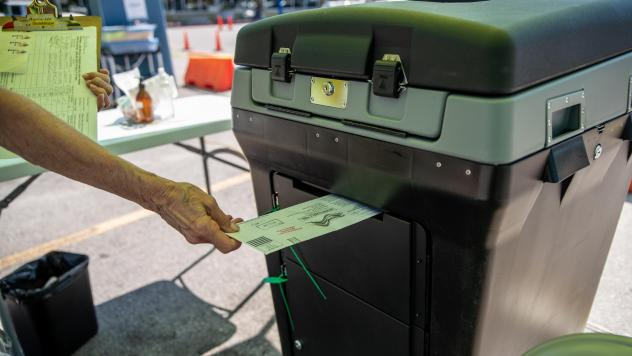 A federal appeals court is allowing Texas Gov. Greg Abbott's limit of one absentee ballot drop-off spot per county to stand, saying voters have many options. Here, a worker puts a ballot into a lockbox at a drive-through mail ballot hand delivery center