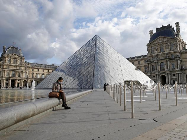 French President Emmanuel Macron is ordering nightly curfews for Paris and other large cities, hoping to control the coronavirus. A woman wears a protective face mask as she sits in the Louvre Museum's courtyard Wednesday in Paris.