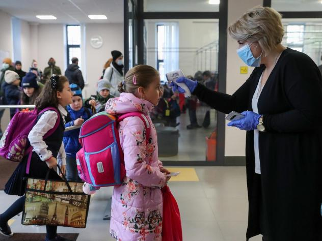 More than 40 million coronavirus infections have now been reported worldwide. Here, a staff member at a school in Moscow uses an infrared thermometer on Monday to screen students.