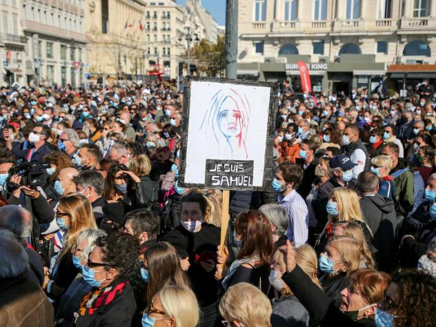 Demonstrators wearing face masks gather Sunday in Marseille, France, to pay tribute to teacher Samuel Paty, who was beheaded after he showed his class cartoons depicting the Prophet Muhammad.