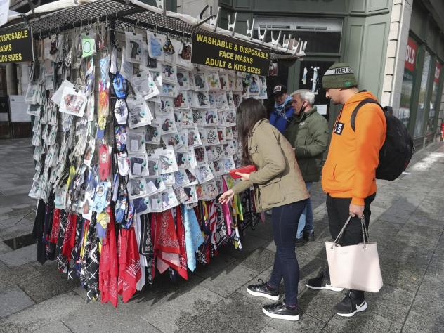 Shoppers buy face masks on O'Connell Street in Dublin, Ireland, on Tuesday. Ireland's government is putting the country at its highest level of coronavirus restrictions for six weeks in a bid to combat a rise in infections.