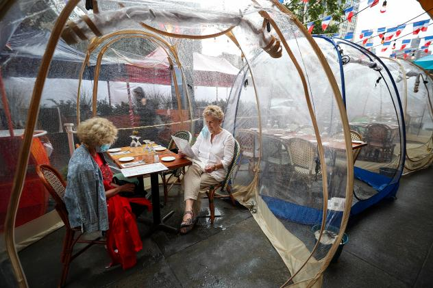 The latest pandemic dining twist is the outdoor bubble, seen here at a New York City restaurant. Sure, it's a way to stay warm as winter looms ... but does it reduce your risk of getting infected by COVID-19?