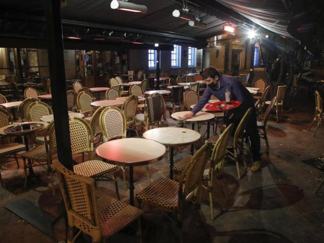 A waiter cleans a table after closing in Saint Germain-en-Laye, west of Paris on Oct. 16,  to comply with new COVID-19 restrictions forcing restaurants, cinemas and theaters in the French capital to close. France imposed a nighttime curfew in Paris and o