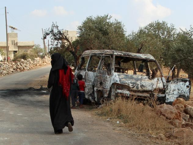 A woman walks past a wrecked van near the northwestern Syrian village of Barisha. Local residents and medical staff told NPR that noncombatant civilians who were in the van were injured and killed last year the night of the U.S. raid on the compound of I