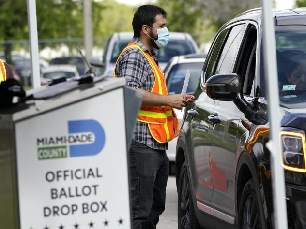An election worker takes ballots from voters dropping them off at an official ballot drop box this week at the Miami-Dade County Board of Elections in Doral, Fla.