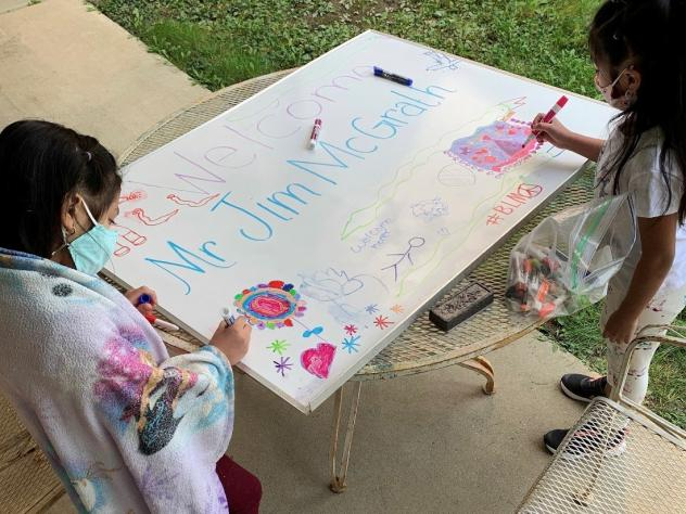 Nicole, a kindergartner, and Angelique, a third grader, make a poster welcoming a regular visitor to the learning hub who teaches the children how to care for their pets: Persephone the guinea pig and George Kiwi the turtle.