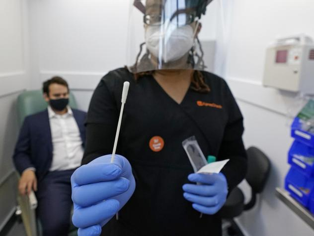A medical assistant holds a swab after testing a man on Wednesday at the new COVID-19 testing facility at Boston Logan International Airport.