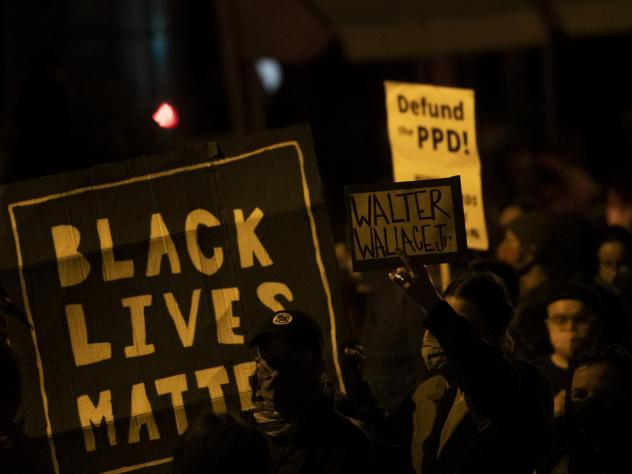 "Demonstrators hold placards reading ""BLACK LIVES MATTER,"" ""Walter Wallace JR."" and DEFUND PPD"" as they gather in protest near the location where Wallace, a 27-year-old Black man, was killed by two police officers in Philadelphia. Police officers said he"