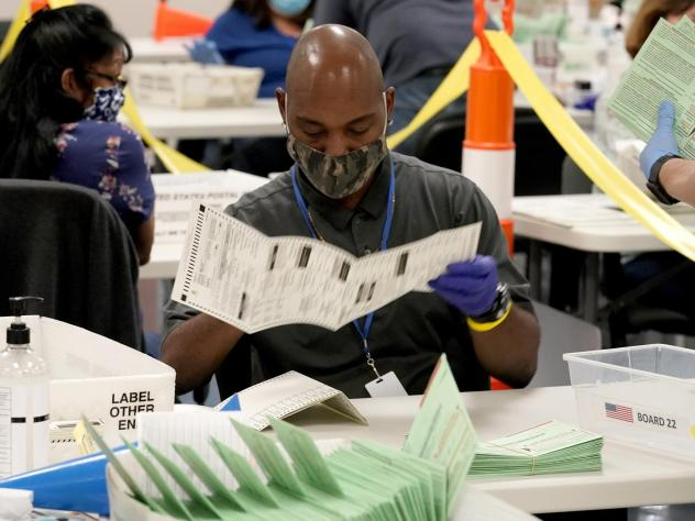 Election workers sort ballots at the Maricopa County Recorder's Office in Phoenix. Mail-in ballots in Arizona are already being counted.