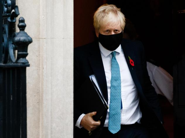 British Prime Minister Boris Johnson wears a mask and remembrance poppy as he leaves No. 10 Downing St. heading for the Houses of Parliament in London after ordering a new England-wide coronavirus lockdown.