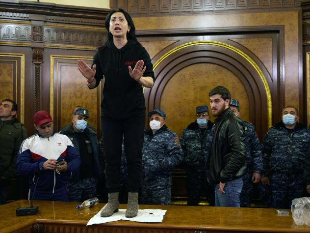Police look on as a woman shouts among protesters who have stormed Armenian Prime Minister Nikol Pashinyan's office after the announcement of a peace deal in the war between Armenia and Azerbaijan on Tuesday.