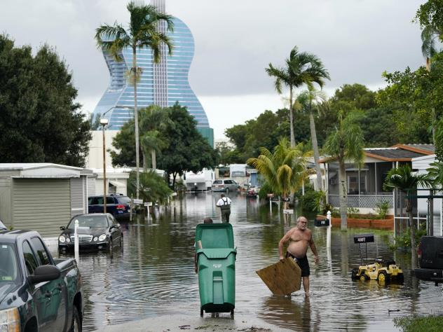 Residents clear debris from a flooded street in the Driftwood Acres Mobile Home Park, in the aftermath of Tropical Storm Eta, on Tuesday in Davie, Fla.