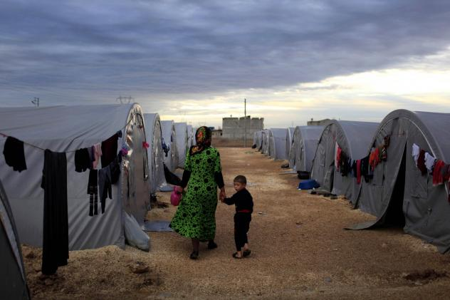 A Kurdish refugee mother and son from the Syrian town of Kobani walk beside their tent in a camp in the Turkish town of Suruc on the Turkish-Syrian border in 2014. President-elect Joe Biden aims to reverse the Trump administration's dramatic cuts to refu