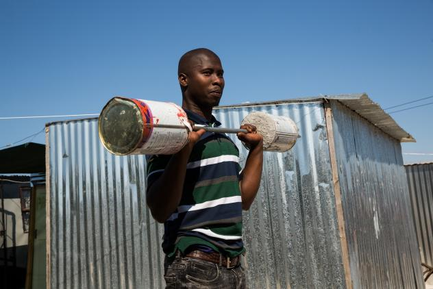 Alfred Sonandi plays around with a makeshift barbell — concrete poured into two tins on either end of a stick. People in the settlement of Covid don't usually wear masks: Living in such close quarters, they may (incorrectly) feel there's no point. They