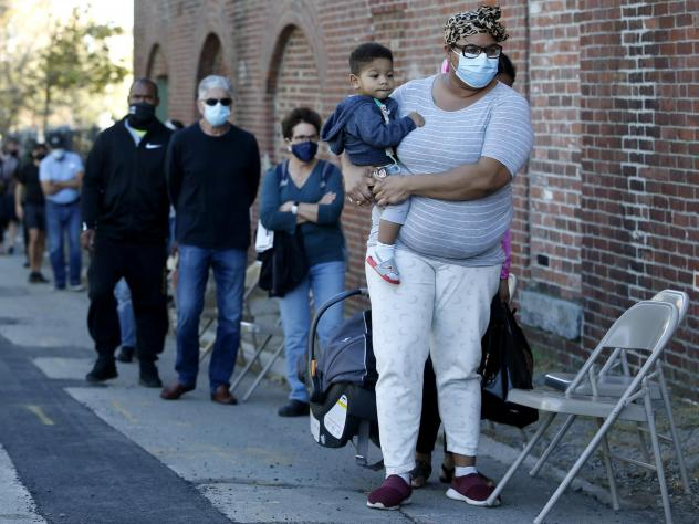 A woman holds her 1-year-old son as they wait in line to get a coronavirus test.