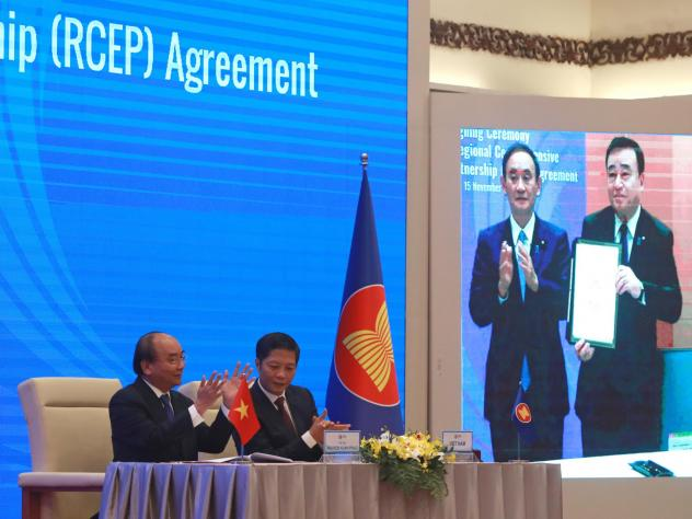 Vietnamese Prime Minister Nguyen Xuan Phuc (left) and Trade Minister Tran Tuan Anh applaud next to a screen showing Japanese Prime Minister Yoshihide Suga and Trade Minister Hiroshi Kajiyama holding up signed RCEP agreement, in Hanoi, Vietnam. China and