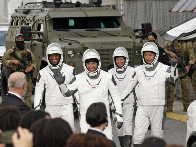 Astronauts, from left, Victor Glover, Michael Hopkins, Shannon Walker, and Japan's  Soichi Noguchi wave to family and friends as they leave for the launch site on Sunday.