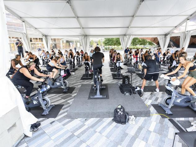 People attend a SoulCycle class under an outdoor tent in September in New York City.
