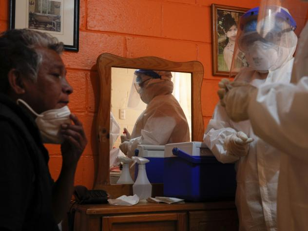 Ricardo Leon Luna, 74, lowers his mask as Doctors Delia Caudillo, right, and Monserrat Castaneda, prepare to take throat and nasal swabs as they conduct a COVID-19 test in his home in the Venustiano Carranza borough of Mexico City, on Thursday.