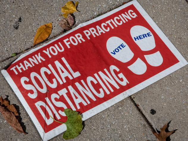 """A social distancing sign on the ground. """"Social distancing"""" was one of dozens of terms highlighted by researchers in Oxford Languages' 2020 Word of the Year campaign."""