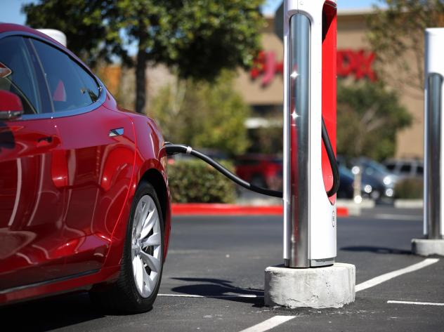 A Tesla car powers up at a charging station in Petaluma, Calif. on Sept. 23, 2020. Auto makers are trying to convince would-be electric car buyers to adopt new habits to power their vehicles.