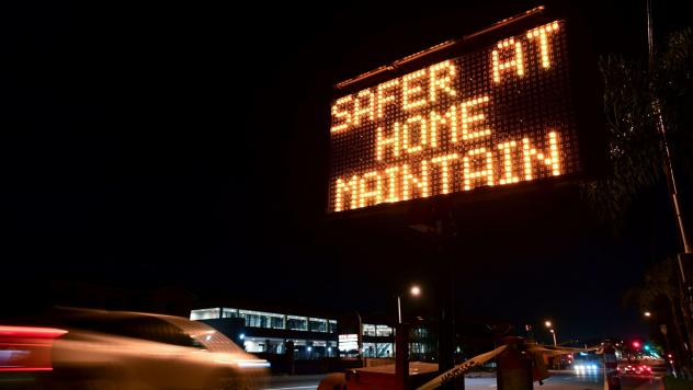 A sign reminds motorists of Los Angeles County's stay-at-home regulation. On Wednesday, the Centers for Disease Control and Prevention rolled out its revised guidelines for people potentially exposed to the coronavirus.