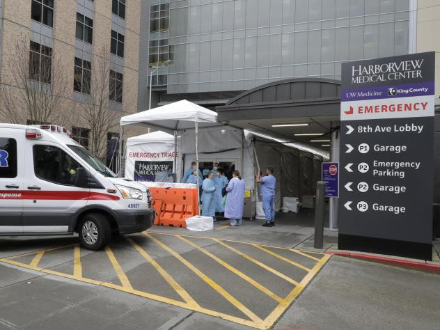 An ambulance pulls up as nurses outside a triage tent for the Emergency Department at the Harborview Medical Center in Seattle put on gowns and other protective gear at the start of their shift, on April 2, 2020. A resurgence of the coronavirus has healt