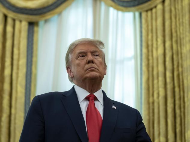 President Trump listens during a ceremony Thursday to present the Presidential Medal of Freedom to former college football coach Lou Holtz in the Oval Office.