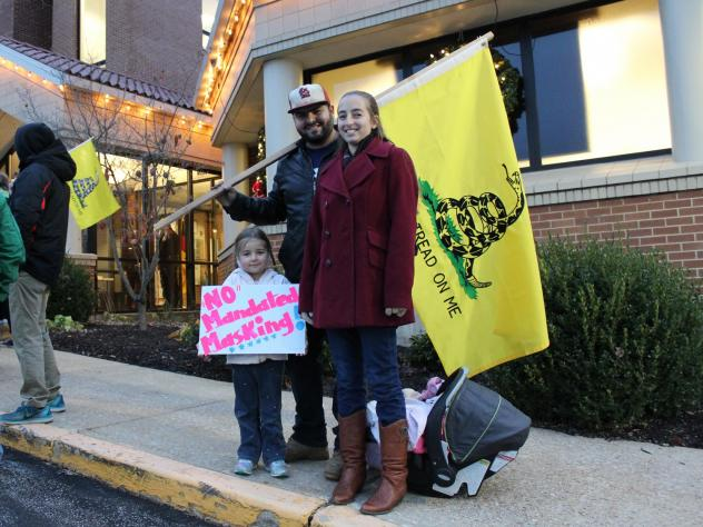 """Outside City Hall on the evening of a vote on a proposed mask order in Washington, Mo., residents Ali and Duncan Whittington protest against the order, along with their 4-year-old daughter. """"I'm here because I feel my freedom is being violated,"""" Ali says"""