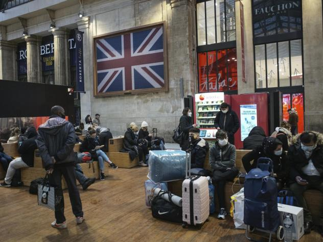 Passengers wearing face masks wait next to the Eurostar Terminal at Gare du Nord train station in Paris on Monday. France is banning all travel from the U.K. for 48 hours in an attempt to make sure that a new strain of the coronavirus in Britain doesn't