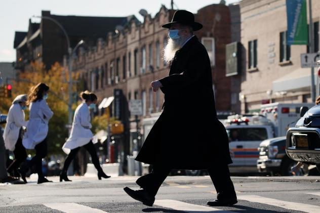 A Hasidic man and medical workers cross paths near the Maimonides Medical Center in Brooklyn, N.Y., in November. When public health messaging comes from community leaders, it's much more likely to be adopted, research on diverse groups finds.